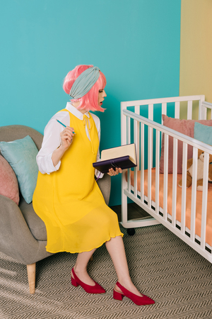 retro styled pregnant pin up woman with pink hair holding notebook and pencil near baby cot Stock Photo