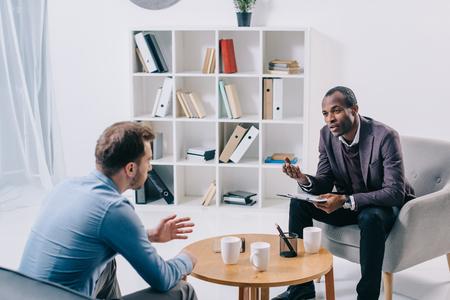 Psiquiatra afroamericano hablando con cliente masculino joven