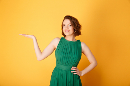 portrait of smiling woman with outstretched arm isolated on orange
