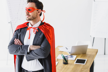 super businessman standing with crossed arms in mask and cape in office Reklamní fotografie