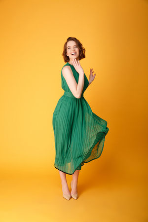 happy young beautiful woman in green dress isolated on orange