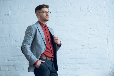 Stylish man in casual clothes wearing glasses by brick wall