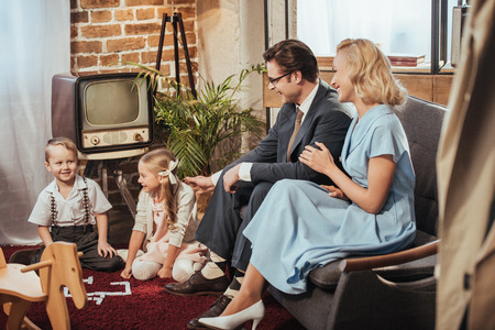 happy 50s style parents sitting on sofa and looking at adorable children playing at home