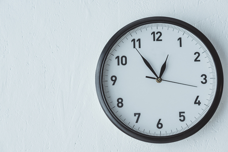 Analog clock on white wall background with copy space