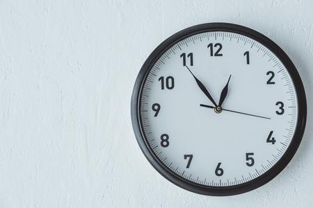 Orologio analogico su sfondo muro bianco con spazio copia