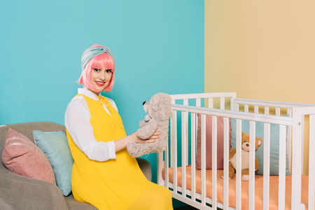 happy retro styled pregnant pin up woman with pink hair sitting with teddy bear near baby cot