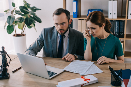 lawyer and crying client discussing contract at workplace with laptop in office