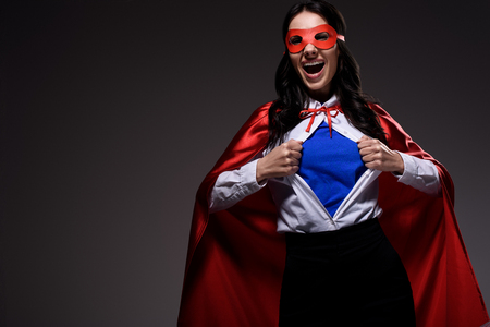 laughing attractive super businesswoman in red cape and mask showing blue shirt isolated on black