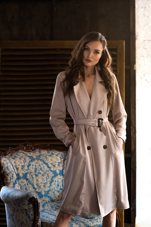 beautiful model in classic trench coat posing near armchair Foto de archivo