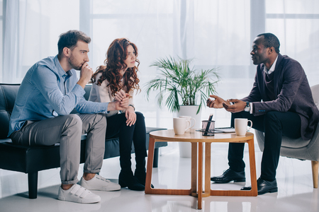 Smiling african american psychiatrist talking to young couple in office