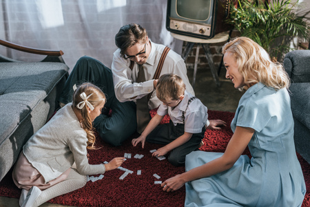 happy family with two children playing dominoes together at home, 1950s Stock Photo
