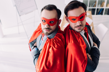 high angle view of serious super businessmen in masks and capes with crossed arms in office