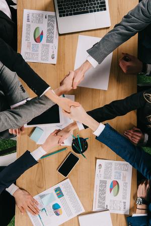 Vue recadrée de partenaires commerciaux se serrant la main à table au bureau Banque d'images
