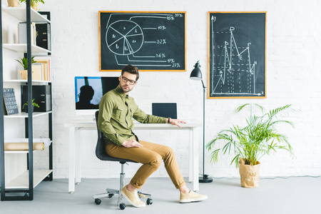 Man in glasses sitting by table with computer and laptop in light office
