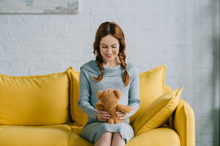beautiful pregnant woman sitting with teddy bear in living room Stok Fotoğraf