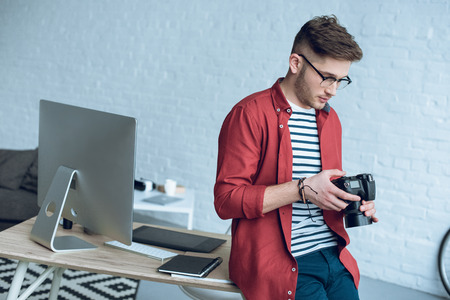 Young man holding camera and leaning on table with computer at home office Stock Photo