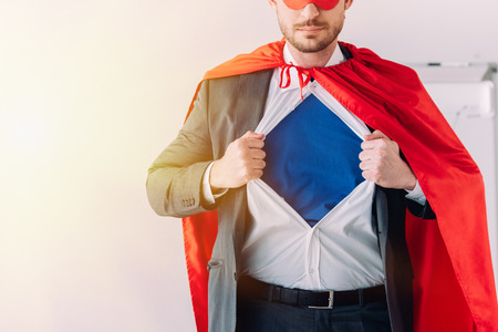 cropped image of super businessman in mask and cape showing blue shirt in office Stock Photo