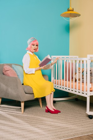 retro styled pregnant pin up woman with pink hair holding book near baby cot in child room
