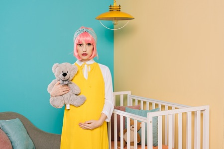 retro styled pregnant pin up woman with pink hair holding teddy bear in child room Stock Photo