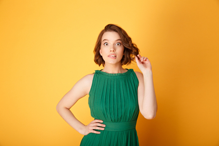 portrait of young surprised woman akimbo isolated on orange