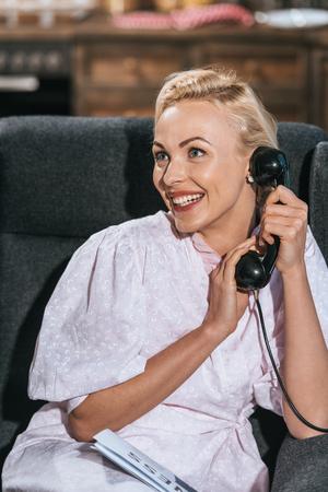 happy blonde woman in robe talking by vintage telephone and looking away 版權商用圖片