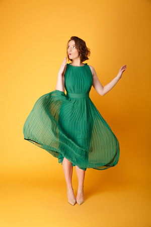 young beautiful woman in green dress with oops gesture isolated on orange