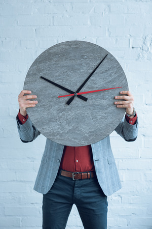 Man holding large clock in front of his face Stock fotó