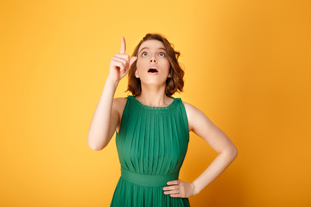 portrait of young emotional woman akimbo pointing up isolated on orange Foto de archivo