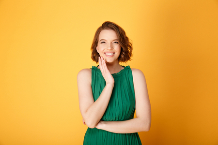 portrait of pretty smiling woman looking at camera isolated on orange Stock Photo