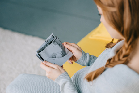 cropped image of pregnant woman holding photo of newborn baby in living room