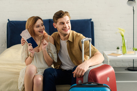 young cheerful couple with travel bags sitting on bed and holding tickets with passports 스톡 콘텐츠