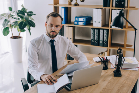 portrait of lawyer with documents sitting at workplace with laptop in office