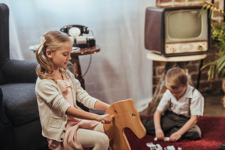cute little girl sitting on rocking horse and brother playing with domino tiles behind at home, 1950s style
