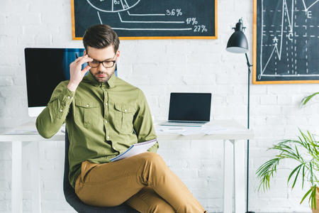 Man in glasses looking at papers by working table in light office