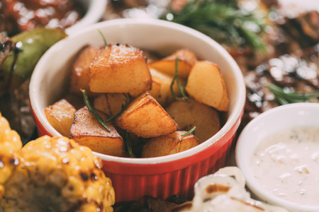 close-up view of delicious roasted potatoes with grilled vegetables and meat