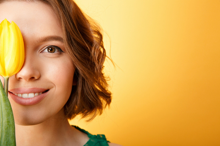 partial view of smiling woman with yellow tulip isolated on orange Stock Photo