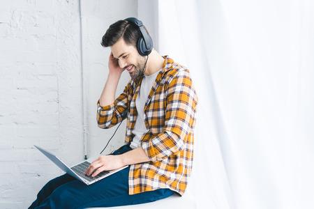 Smiling man in headphones working on laptop by window