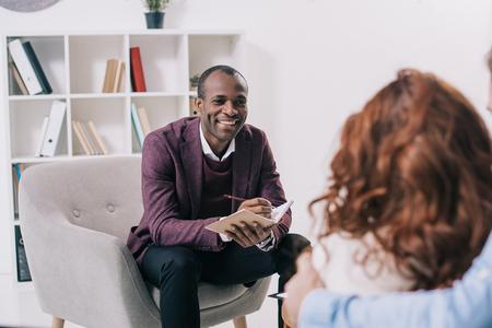 Psiquiatra afroamericano sonriente hablando con pareja joven