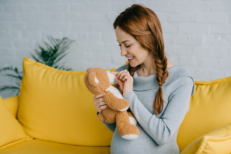 side view of beautiful pregnant woman playing with teddy bear in living room