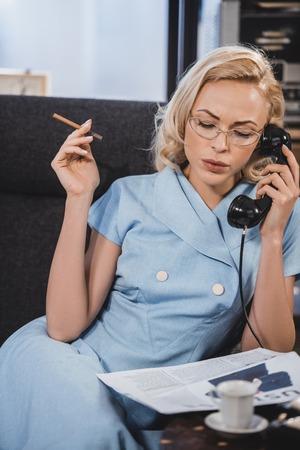 beautiful blonde woman in eyeglasses smoking cigarette and talking by vintage telephone