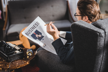 man in suit and eyeglasses holding cigarette and reading business newspaper 写真素材