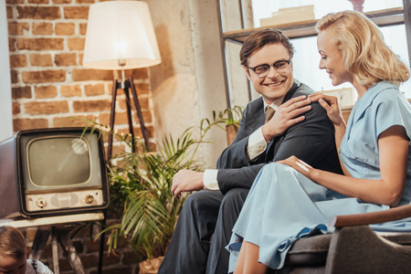 happy 50s style couple sitting on sofa and smiling each other