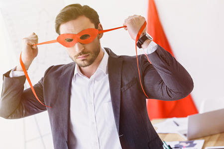 super businessman tying red mask in office Stock Photo