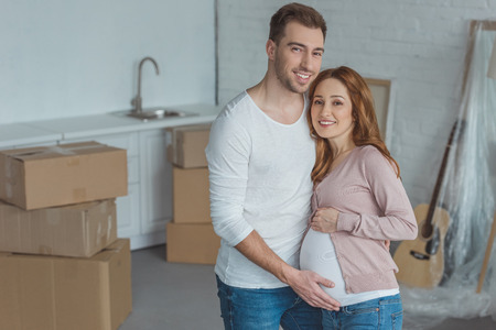 happy pregnant couple smiling at camera in new house Standard-Bild