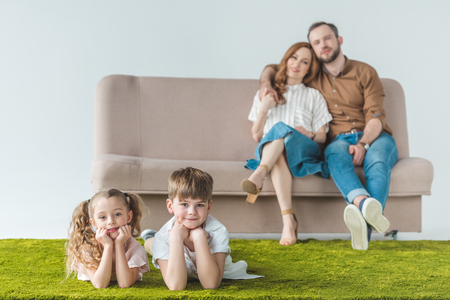 happy parents sitting on couch and looking at beautiful children lying on lawn Фото со стока - 111437064