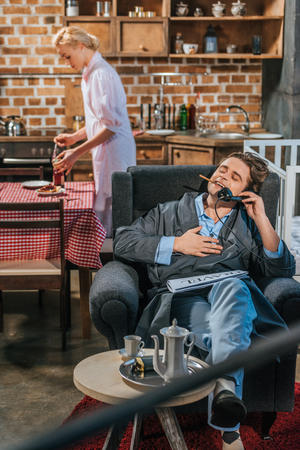 smiling man in robe smoking cigarette and talking by vintage telephone while wife preparing breakfast behind