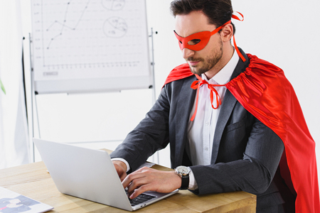 super businessman in mask and cape working with laptop in office Stock Photo