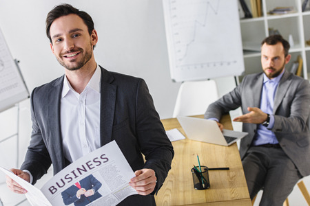 handsome businessmen with newspaper and laptop in office Foto de archivo - 111439949