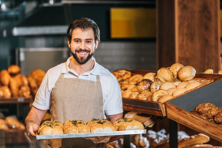 Porträt eines lächelnden Verkäufers, der frisches Gebäck im Supermarkt anordnet? Standard-Bild