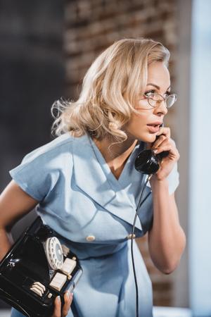 emotional blonde woman in eyeglasses talking by vintage telephone and looking away Stock fotó